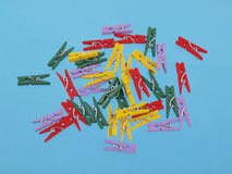 Multicoloured clothes peg shaped paper clips on a blue background. Royalty Free Stock Photos