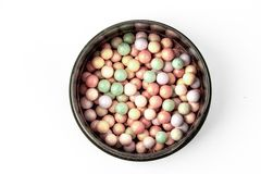 Multicolored concealer powder balls in a box on a white background royalty free stock photography