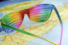 The multicoloured glasses. The multicoloured striped glasses on the map Stock Images