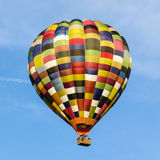 Multicoloured hot air balloon in a clear blue sky. A patchwork multicoloured hot air balloon  in the UK in a clear blue sky Stock Photos