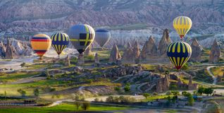 Multicoloured hot air balloons at sunrise flying over Cappadocia, Goreme, stock photography