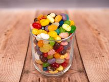Jelly Beans in a jar. Multicoloured jelly beans in a glass on a wooden background Royalty Free Stock Photography
