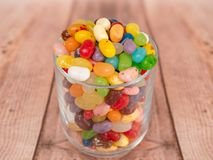 Jelly Beans in a jar. Multicoloured jelly beans in a glass on a wooden background Royalty Free Stock Image