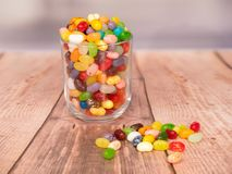 Jelly Beans in a jar. Multicoloured jelly beans in a glass on a wooden background, with some spilled on the surface Royalty Free Stock Photo