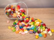 Jelly Beans in  jar. Multicoloured jelly beans in a glass on a wooden background, with some spilled on the surface Stock Image