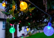 Outdoor solar party lights seen in a garden. stock images