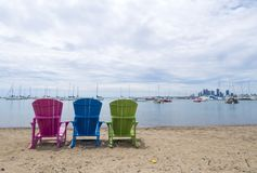 Multicoloured Muskoka Cottage chairs on the sand the beach looking out to the harbor and downtown Etobicoke in the background stock photos