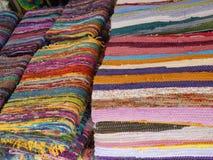 Multicoloured opgerolde tapijten stock afbeeldingen