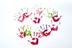 Multicoloured painted hand prints isolated on white stock images