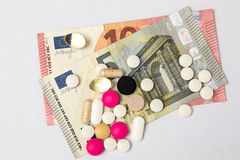 Multicoloured pills and hard capsules and euro banknotes. On white background Stock Photo