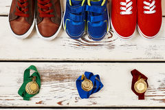 Multicoloured sneakers and medals. Steps to goal achievement Stock Image