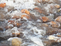 Multicoloured stones, waves with foam Royalty Free Stock Image