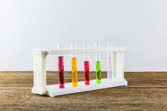 Multicoloured test tubes in the stand on wooden table. Multicoloured test tubes in the stand isolated on wooden table with copy space for your text Stock Photography