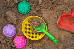 Multicoloured toy lying on a wet sand Royalty Free Stock Photo