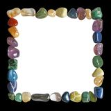Crystal healing black and white square frame. Multicoloured tumbled crystal healing stones placed in a neat square formation border with black outside and white stock image