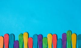Multicoloured wood ice-cream Popsicle stick on blue background. Copy space for text Stock Photos