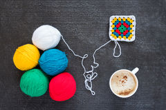 Multicoloured yarn, a crocheted motif and coffee Stock Photos
