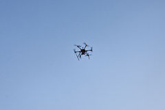 Multicopter is flying in blue sky Stock Images