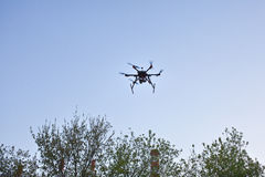 Multicopter is flying in blue sky Royalty Free Stock Images