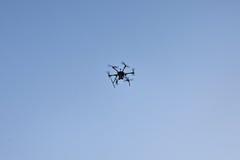 Multicopter vliegt in blauwe hemel Stock Afbeeldingen