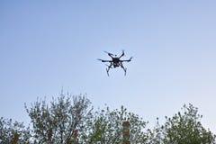 Multicopter vliegt in blauwe hemel Royalty-vrije Stock Afbeeldingen