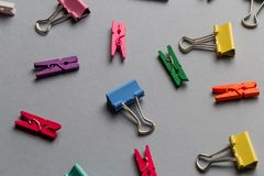 Multiculored paper clips and clothespins on grey background royalty free stock images