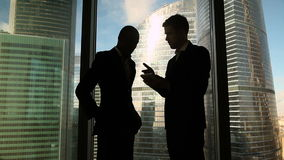 Multicultural business partners handshaking on meeting against full length window. Multicultural two business partners handshaking standing near office full stock video