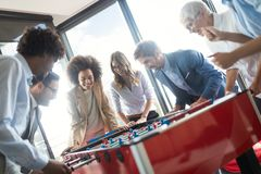 Multicultural business people celebrating win while playing table football. Together royalty free stock photo