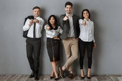Multicultural business people in formal wear pointing at camera while standing. At grey wall royalty free stock image