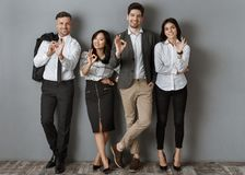 Multicultural business people in formal wear showing ok sign while standing. At grey wall stock photo