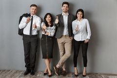 Multicultural business people in formal wear showing thumbs up while standing. At grey wall royalty free stock images