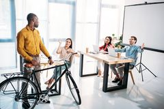 Multicultural business people greeting african american colleague with bicycle. In office royalty free stock photo