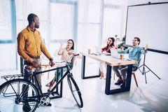 Multicultural business people greeting african american colleague with bicycle. In office stock photos