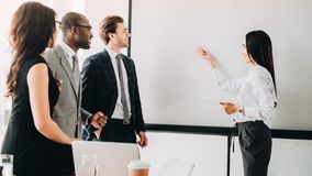 Multicultural business people looking at empty white board during business meeting. In office royalty free stock photo