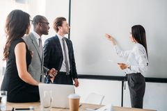 Multicultural business people looking at empty white board during business meeting. In office royalty free stock photography