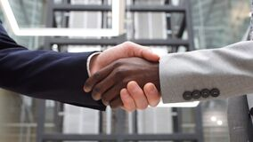 Multicultural businessmen shaking hands during contract signing at workplace. Two Multinational Business People Handshake. Greeting Deal Concept stock video footage