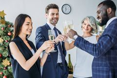 Multicultural businesspeople clinking with glasses of champagne with christmas tree on background. In office royalty free stock photos