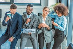 Multicultural businesspeople with coffee newspaper and smartphone. In office stock image