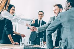 Multicultural businesspeople shaking hands in conference hall while team leader showing. Thumb up royalty free stock photo