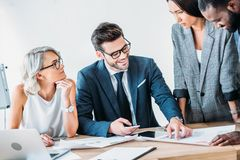 Multicultural businesspeople working on project in office and standing near table. With documents stock image