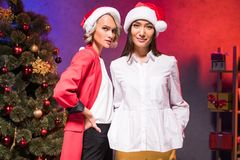 Multicultural businesswomen in santa hats looking at camera at new year. Corporate party royalty free stock images