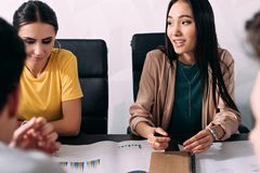 Multicultural businesswomen sitting at table with graphs during business meeting at modern. Office stock images