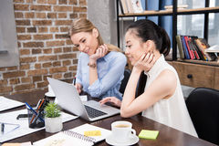 Multicultural businesswomen working with laptop and sitting at workplace. Smiling multicultural businesswomen working with laptop and sitting at workplace royalty free stock photography