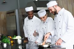 Multicultural chefs frying vegetables on frying pan. At restaurant kitchen royalty free stock images