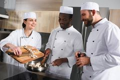 Multicultural chefs preparing mushrooms. At restaurant kitchen stock photography