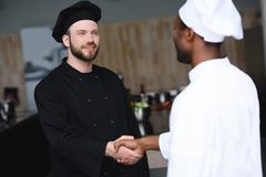 multicultural chefs shaking hands stock image