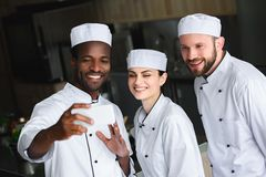 Multicultural chefs taking selfie with smartphone. At restaurant kitchen royalty free stock photography