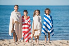 multicultural children in colorful towels standing at seaside and looking royalty free stock images