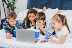 Multicultural children drinking soda and watching movie. At home together stock images