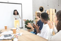 Multicultural colleagues applauding to african american businesswoman. During presentation in office stock image